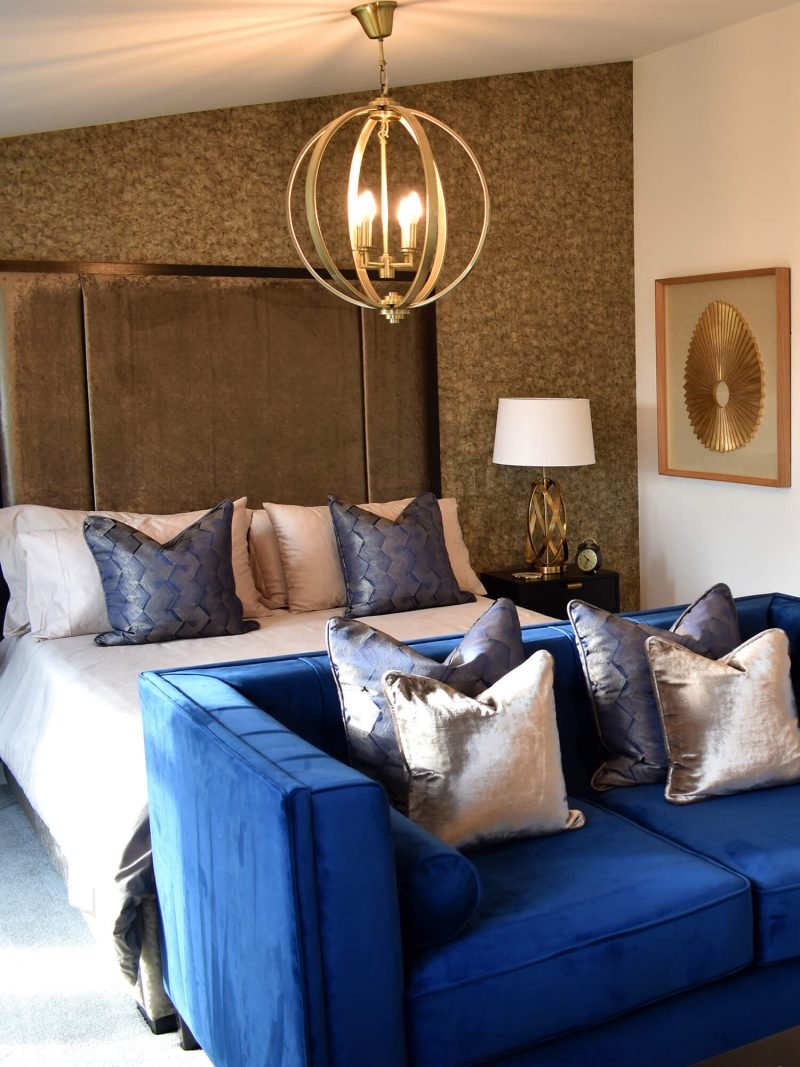 Master bedroom with gold lamp and purple couch
