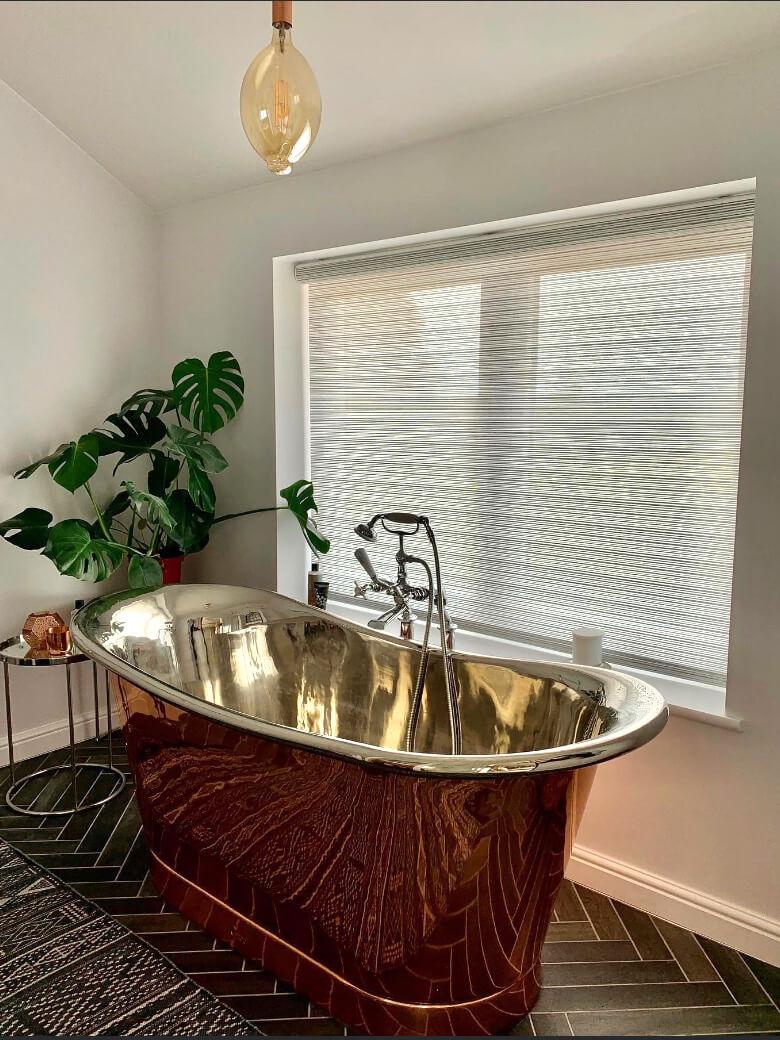 Roller blind next to brass bath tub